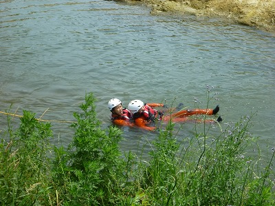 ロープを携行した隊員が要救助者に接触し、陸上にいる隊員と協力して川岸まで救出している様子