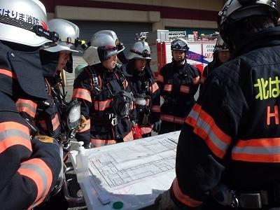現場指揮所で各隊が集合し、図面で建物構造を確認