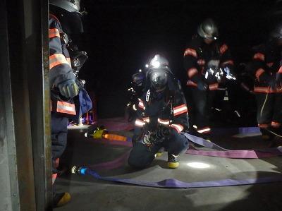 暗所で進入前の放水体系をとる消防隊員