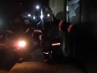 進入する前にドアの熱感を確認する消防隊員